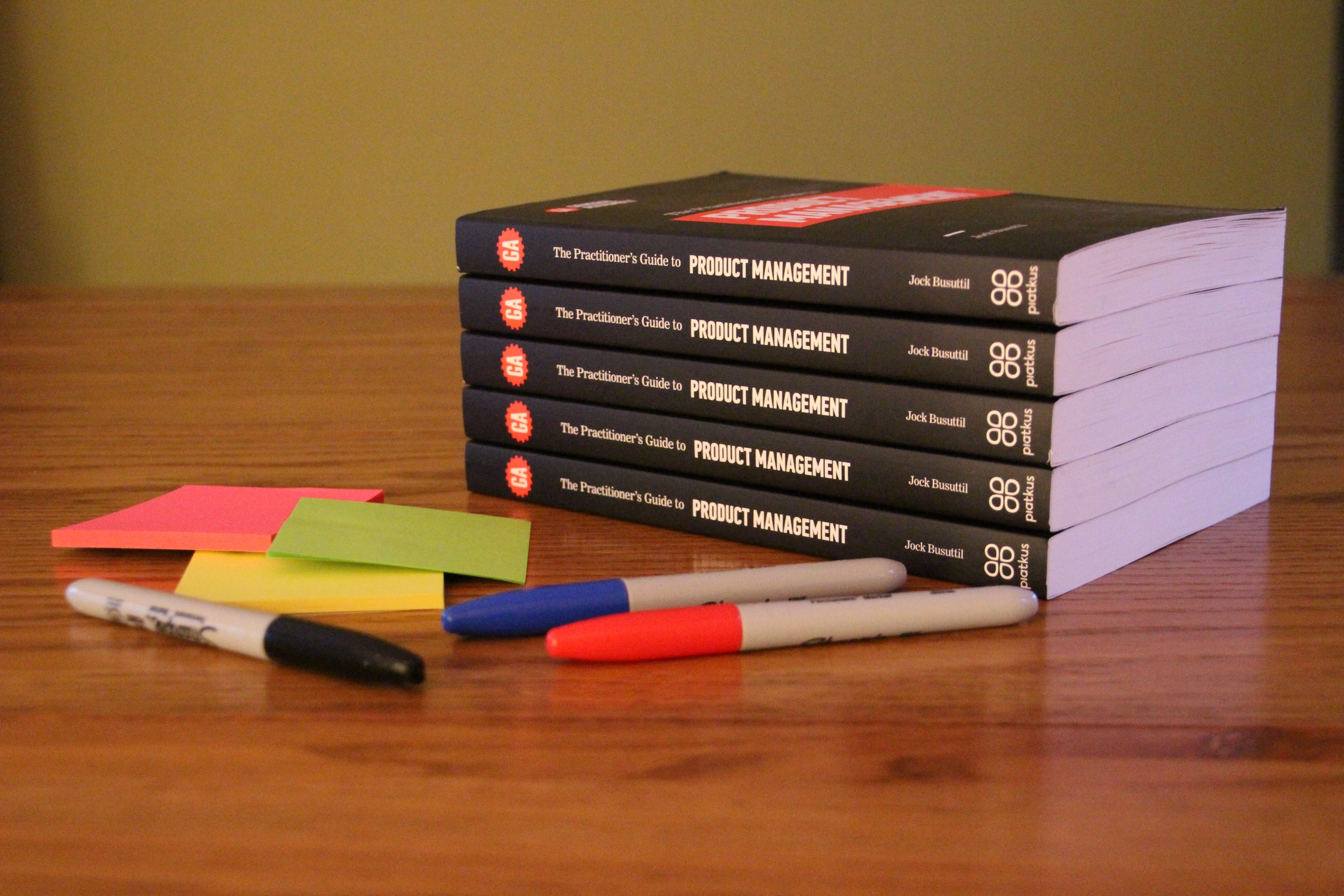 "A pile of books ""The Practitioner's Guide to Product Management"" sits on a table next to some colourful sticky notes and Sharpie pens (Photo by Jock Busuttil / Product People Limited)"