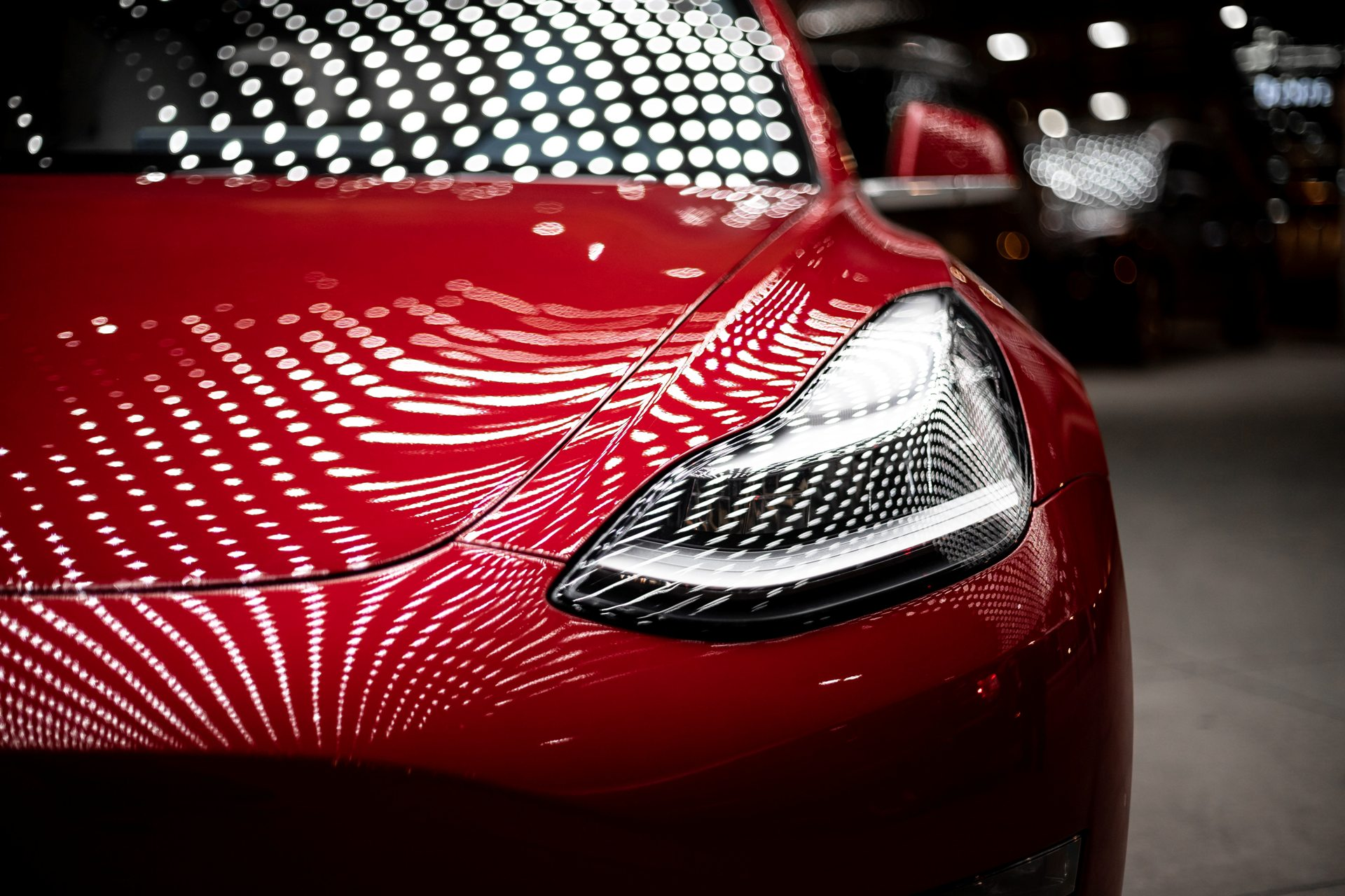 Red Tesla car illuminated by grid of lights